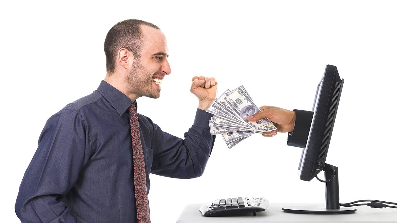 Person Feeling happy while sitting at a computer, and from a computer screen, there is a hand that extends holdin and offering dollars money